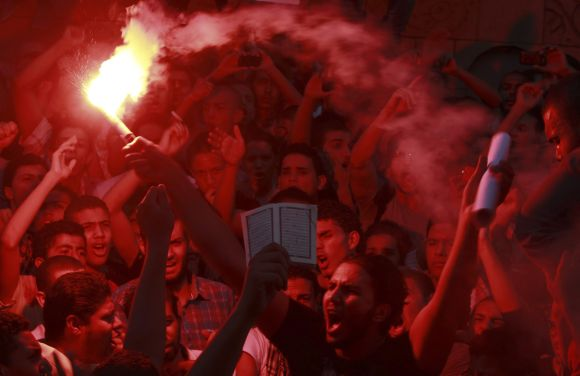 People shout slogans and light flares in front of the U.S. embassy during a protest in Cairo