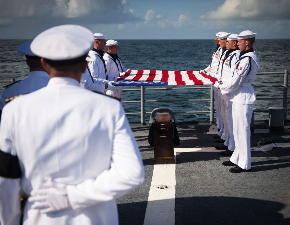 Members of the US Navy ceremonial guard hold an American flag over the remains of Neil Armstrong in the Atlantic Ocean