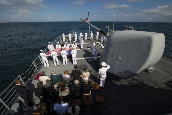Family members of late Neil Armstrong and members of the US Navy are seen during the burial at sea service