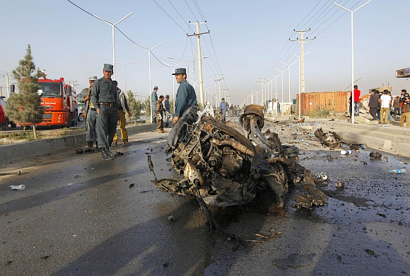 Afghan police stand near the wreckage of a vehicle which was used by a suicide bomber near Kabul
