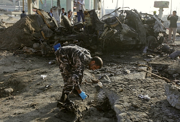 An Afghan security officer investigates the site of the suicide attack