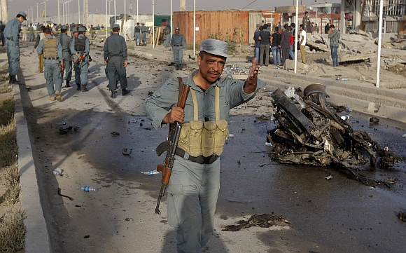 An Afghan police officer keeps people away from the site of a suicide attack in Kabul