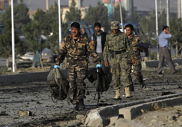 Afghan security personnel carry bags belonging to foreign contractors at the site of a suicide attack