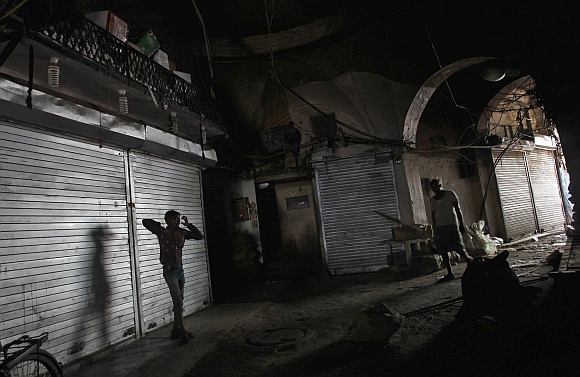 People walk past closed shops during a nationwide strike in the old quarters of Delhi