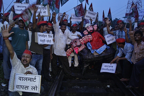 Demonstrators from the Samajwadi Party shout slogans as they gather around an effigy on a railway track during a protest against price hikes in fuel and foreign direct investment near Allahabad railway station
