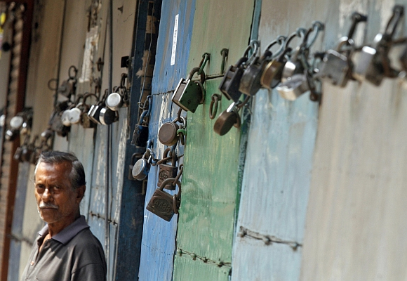 A man stands in front of closed shops during a nationwide strike in Kolkata