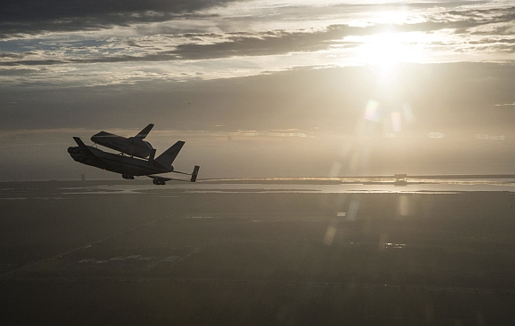 The space shuttle Endeavour, atop NASA's Shuttle Carrier Aircraft, flies over the Kennedy Space Center in Cape Canaveral, Florida