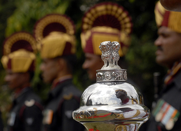 An Indian soldier is reflected on an official emblem of the Government of India