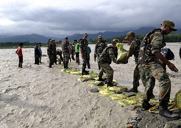 Soldiers build a temporary barricade after it was washed out by heavy rain on the Mahananda river