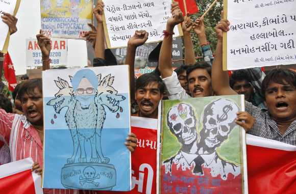 Protestors shout anti-government slogans and hold a caricature of Dr Singh during a nationwide strike