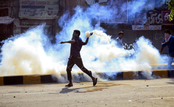 A protester throws a teargas canister, which was thrown by the police earlier, during clashes in Lahore