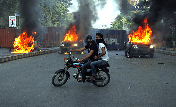 Protesters ride past burning police vehicles during an anti-American protest rally to mark the 'Day of Love' in Karachi