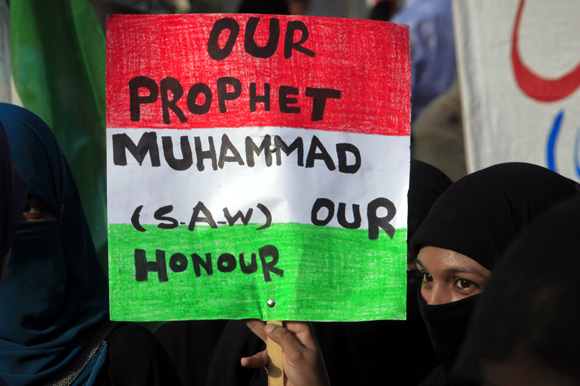 A protester holds a placard while taking part in an anti-American demonstration during a protest rally in Lahore