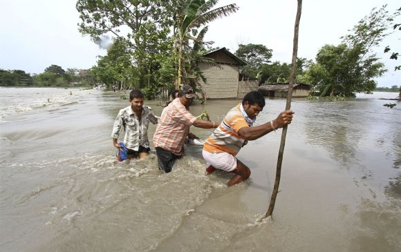 Villagers cross a flooded road at Lachi Bishnupur village in Assam.