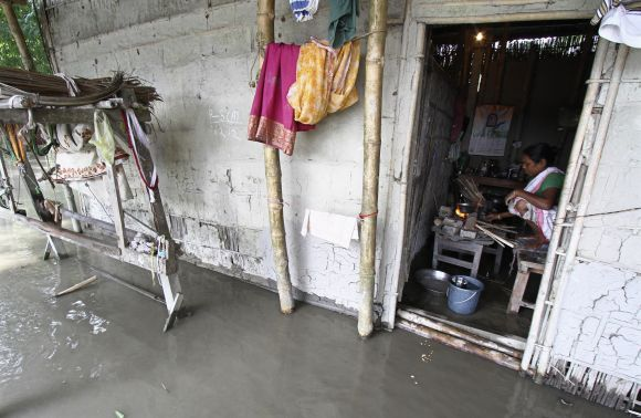 A flood affected woman prepares food inside her submerged hut at Lachi Bishnupur village in Assam