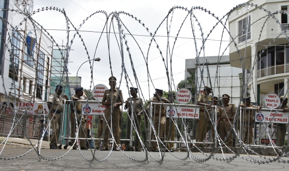 Policemen stand guard behind a coil of concertina wire setup to stop people from protesting against Sri Lankan President Mahinda Rajapaksa