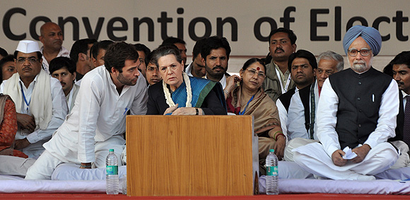 Sonia Gandhi listens to her son, Rahul, as Prime Minister Manmohan Singh looks on.
