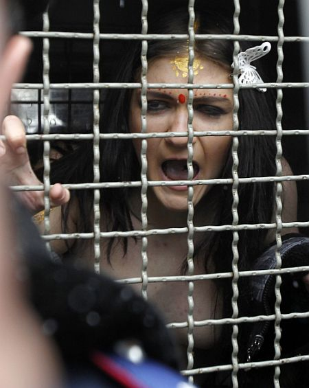 A detained activist from women's rights group Femen shouts from a police van
