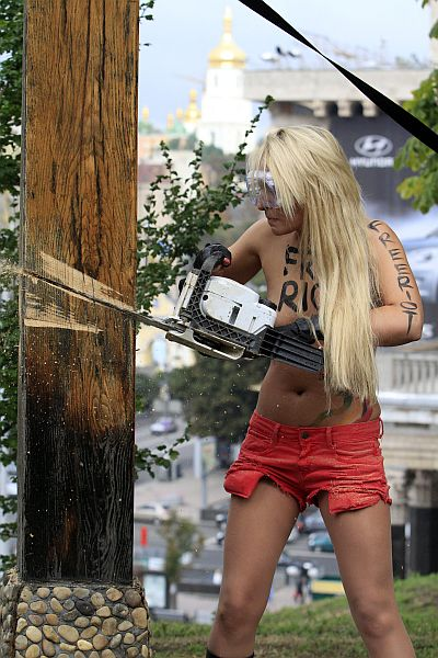 An activist from women's rights group Femen uses a chainsaw to cut down a Christian cross, erected in memory of victims of political repressions under the Soviet dictator Josef Stalin regime, near the Oktyabrsky Palace in central Kiev
