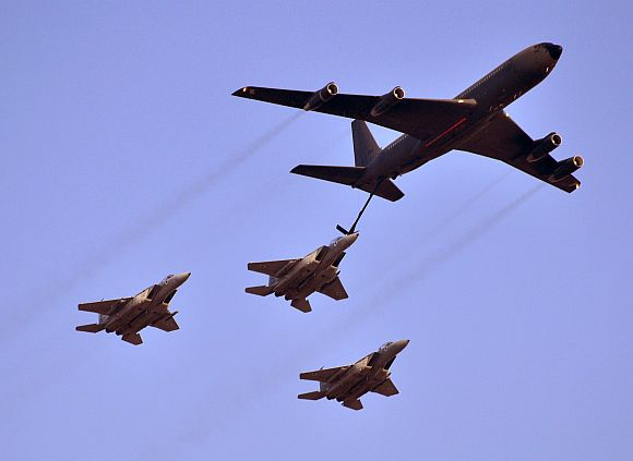 A Boeing 707 aerially refuels 3 Israeli F-15 Eagles