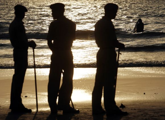 Policemen stand guard at a coast in Mumbai