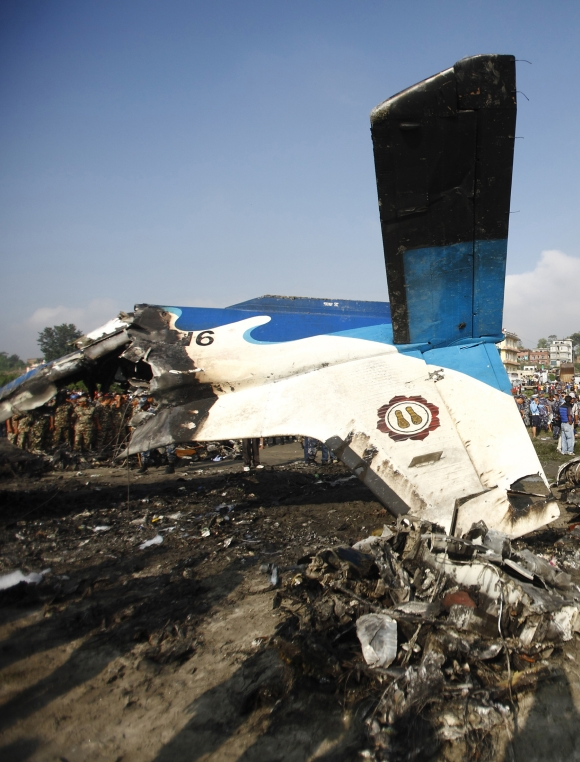 The wreckage of a Dornier aircraft, owned by private firm Sita Air, is seen as a rescue team investigates at its crash site in Kathmandu