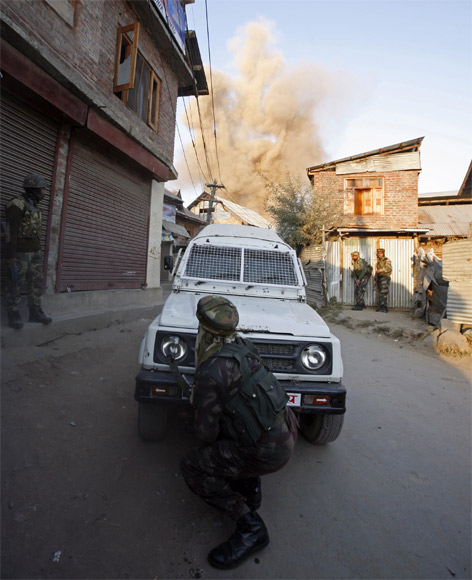 A soldier takes cover as a residential house is blown up by an improvised explosive device during a gun battle between army and suspected militants in Sopore, 48km north of Srinagar