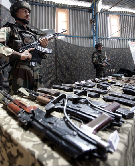 Soldiers stand guard near seized arms and ammunitions at an an army garrison in Kupwara, north of Srinagar