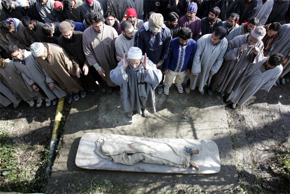 Villagers pray during the funeral of a militant in Sopore