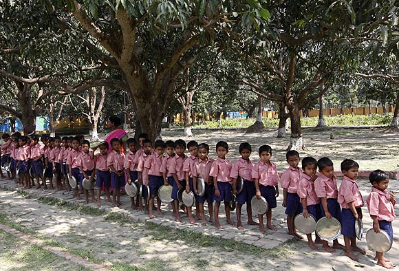 Children stand in line to collect their free mid-day meal in a school