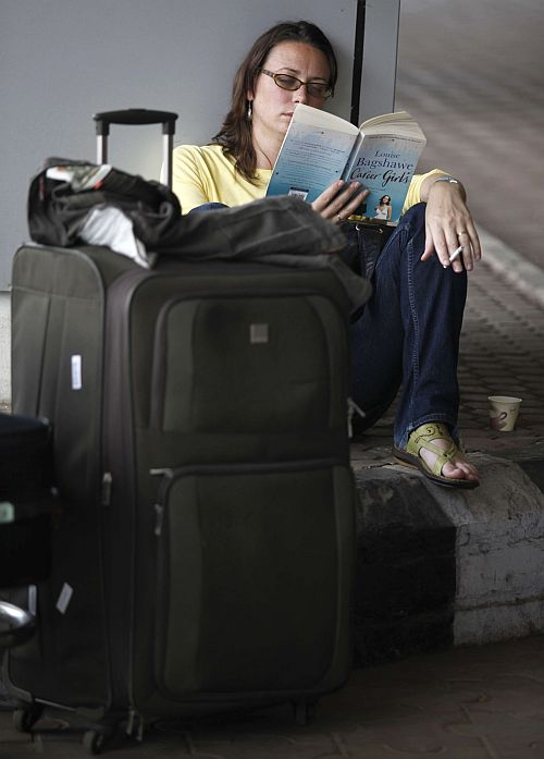 foreign tourist waits for her flight confirmation outside the international airport in Kolkata