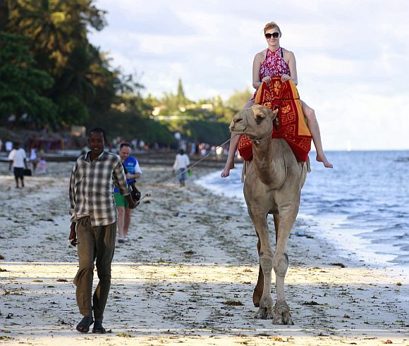 A tourist rides on a camel's back at the Jomo Kenyatta public beach in Kenya's coastal city of Mombasa