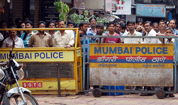 Onlookers stand behind a barricade installed by police at Zaveri Bazaar