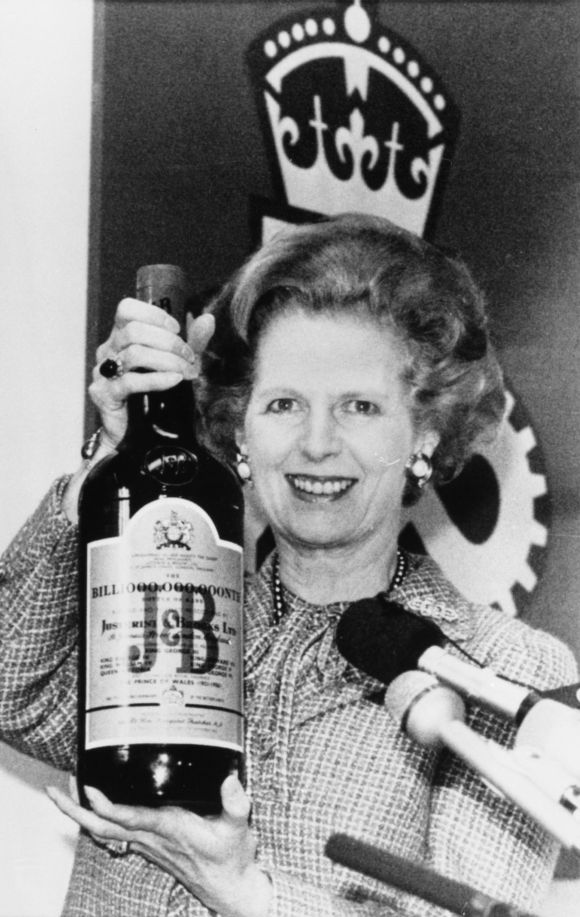 British Prime Minister Margaret Thatcher holds a three litre bottle of scotch whisky which was presented to her after a tour of a whisky distillery