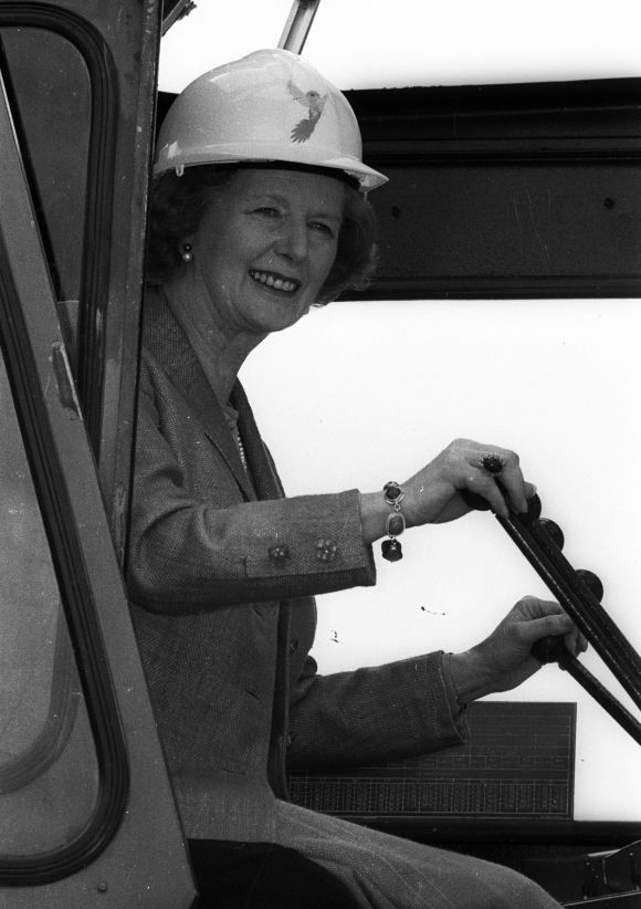 Helping to build an empire, Britain's Prime Minister Margaret Thatcher takes the controls of a crane to place an inaugural block of marble in London on July 11, 1986