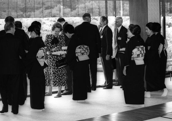 In her stocking feet at the Japanese style dinig room at Akasaka Palace on May 5, 1986, British Prime Minister Margaret Thatcher presents a picture of contrast to the kimono-clad, sandle-wearing hostess