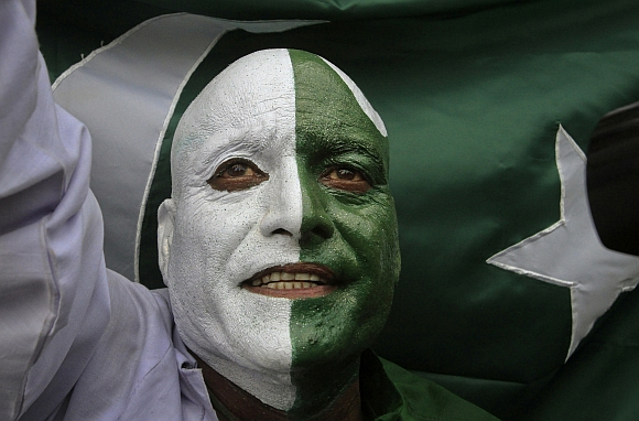 A man, with his face painted depicting the colours of the Pakistan national flag, attends a ceremony to mark the country's Independence Day at the Wagah border crossing with India on the outskirts of Lahore