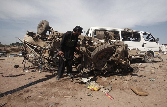 A security official inspects a damaged vehicle at the site of a bomb attack near Jalozai camp in Nowshera district, northwestern Pakistan