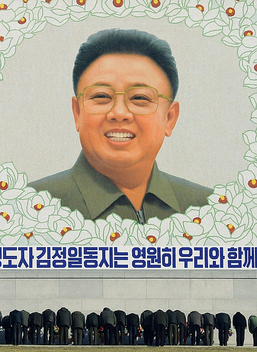 North Koreans bow in front of a portrait of late leader Kim Jong-il in Pyongyang, in this photo taken and provided by Kyodo, on the birthday of their late leader, Kim Jong-il