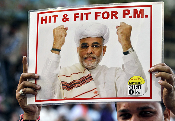 A supporter of holds a poster featuring Narendra Modi outside the BJP office in Ahmedabad