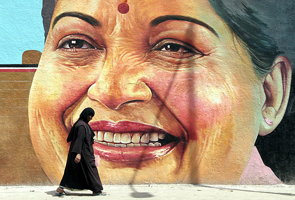 A woman walks past a portrait of Tamil Nadu CM J Jayalalithaa