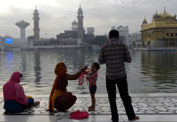 A little tyke has her first dip in the Amrit Sarovar. Her father captures the occasion on his cell phone