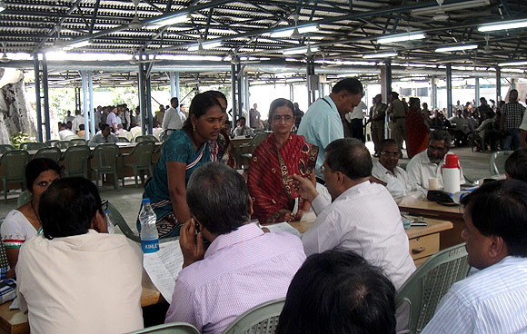 People are directed to different desks manned by government officials