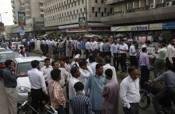 People stand outside of their office buildings following an earthquake tremor in Karachi