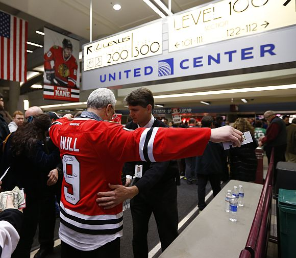 Patrons are searched and patted down with heightened security measures in effect due to the bombings in Boston before the start of the NHL hockey game between the Dallas Stars and the Chicago Blackhawks in Chicago