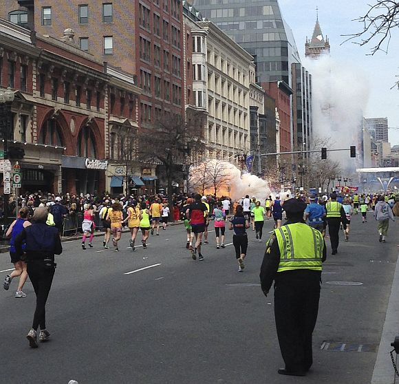 Runners continue to run towards the finish line of the Boston Marathon as an explosion erupts near the finish line of the race in this photo exclusively licensed to Reuters by photographer Dan Lampariello after he took the photo