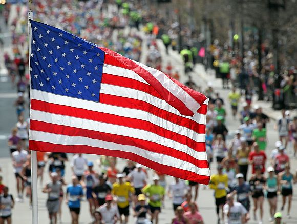 An American flag is seen as runners make their way to the finish line during the 117th running of the Boston Marathon