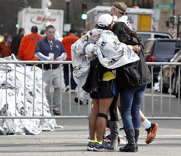 People comfort each other after explosions went off at the 117th Boston Marathon in Boston, Massachusetts