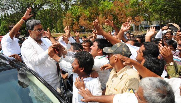 Siddharamaiah greeting people at his constituency in Varuna during a campaign procession