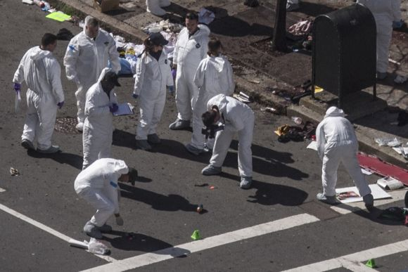 Investigators survey the site of a bomb blast on Boylston Street a day after two explosions hit a marathon in Boston, Massachusetts
